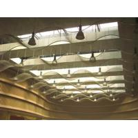 Several pieces of cable metal mesh is formed into waved suspended ceilings.