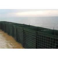 Several green Extra-safe flood & storm barriers are mounted and filled with sand for flood control.