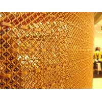 Brass architectural rigid mesh is covering a column.