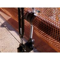 The detail of red metal coil drapery installs on the metal rod at bottom in the outside.