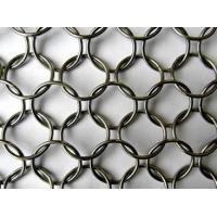 A piece of chain braided metal ring mesh on the gray background.