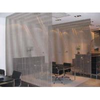 Two pieces of cable metal mesh divide a conference room.