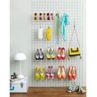 Grid panels leans against the wall with shoes, gloves, glasses and handbag on it