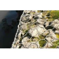 Woven gabion baskets filled with rocks are installed along a river to protect the soil from erosion.
