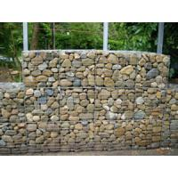 Several gabion baskets are filled with rocks to create a solid retaining wall.