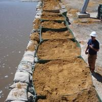 Extra-safe flood barriers are filled with sand, combined with sand bags to resist flood.